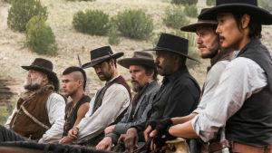 De fantastiska sju (Vincent D'Onofrio, Martin Sensmeier, Manuel Garcia-Rulfo, Ethan Hawke, Denzel Washington, Chris Pratt och Byung-hun Lee) sitter på sina hästar och ser allvarliga ut.