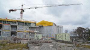 Arbetsplats där en lyftkran syns ovanför bostäderna som byggs på Fabriksudden i Hangö.
