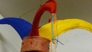 En hatt i rött, gult och blått. Sydd i filttyg. en hatt som narrar använde sig av i gamla hov. Elle jokrar.