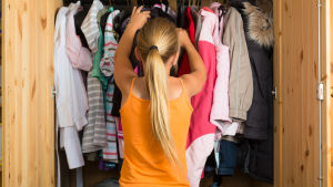 Flicka som står framför klädskåp och väljer kläder.