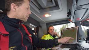 Brandförman Mikko Routala visar på en karta i brandbilen.