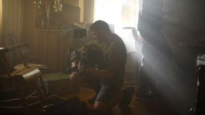 Keskellä kuvaa kameramies pitelee kameraa ja näyttää tutkivan asetuksia. Huone on vanhanaikaisesti sisustettu ja verhojen välistä siivilöityy valo.