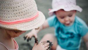 kaksi lasta leikkii hellehatut päässä