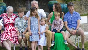 Familj försöker posera för gruppfotografi, alla ser åt olika håll