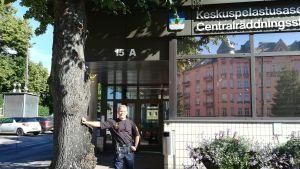 Brandmästare Vesa Berg står lutad mot ett trädd utanför Centralräddningsstationen i Berghäll.