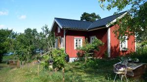 En röd sommarstuga med vita knutar ute på landsbygden.