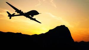 En drönare flyger i solnedgång över berg