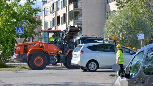 en traktor som håller på med vägarbeten och en person som styr trafiken