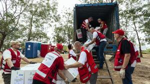 röda kors-personal lyfter förnödenhert ur lastbil