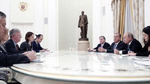 John Bolton, Vladimir Putin, Sergej Lavrov och medarbetare sitter vid ett runt, vitt bord.