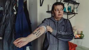 Carolina Sinisalo visar en tatuering på armen där Robins namn, födelse- och dödsdatum är tatuerade.