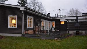 Familjens Formsans hus, ett brunt och lågt stockhus med vita smårutiga fönster.