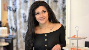 Kvinna med långt mörkt hår ler mot kameran.