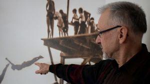 Ole Högberg pekar ut sin bror på fotot som han låtit sätta upp på väggen som tapet.
