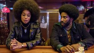 Laura Harrier ja John David Washington istuvat pöydän ääressä. Kuva elokuvasta Blackkklansman.