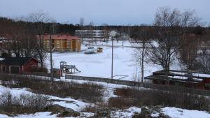 En snöbeklädd miljö. Till vänster i bild en gul trähusbyggnad. Till höger i bild en röd låg byggnad. Mittemellan en öppning.