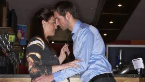 Ett ungt par (man och kvinna) flirtar med varandra i en bar