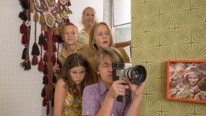 Lapsijoukko kurkistaa kulman takaa, etualalla poika kaitafilmikamera kädessä. Kuva elokuvasta Liekehtivät lapset.