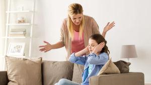 mamma försöker prata med sitt tonåriga barn som håller sig för öronen