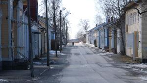 En gata i Kaskö med trähus på båda sidorna. En ensam cyklist skymtar fram på vägen.