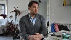 Man i grå tröja och rutig skjorta sitter vid ett bord med händerna knäppta i knät.
