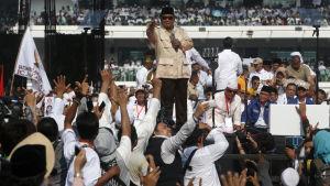 En bild på presidentkandidaten Prabowo Subianto som ställer upp i de Indonesiska valet i april. Här är han omgiven av supportrar.