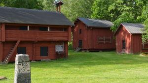 Gamla lador och gårdsbyggnader i stock och målade med rödmylla på en gård. Sommar.