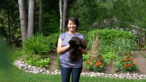Hanne Aho står i sin trädgård och håller den svarta katten Halla i famnen.