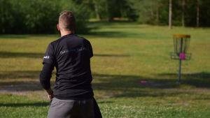 Frisbeegolfaren Joni Lipponen kastar en putter i korgen.