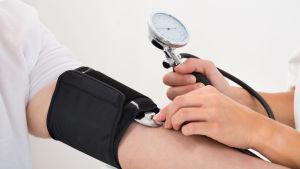 Läkare mäter blodtrycket på en patient.