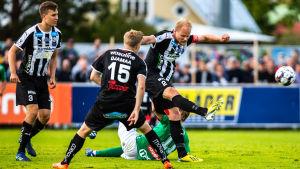 Timi Lahti dunkar iväg bollen, Hindrek Ojamaa och Eero-Matti Auvinen tittar på.