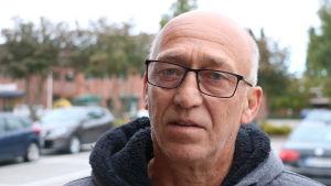 En skallig man med glasögon står på en parkering.
