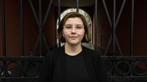 Hanna Lagerström står svartklädd framför ett stängsel och tittar in i kameran.