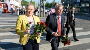 Jutta Urpilainen och Antti Rinne delar ut rosor i Helsingfors 2014.