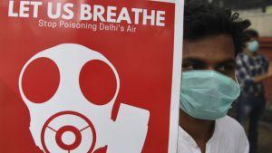 """""""Låt oss andas. Sluta förgifta luften i New Delhi""""står det på skylten som bärs av en man med andningsskydd i New Delhi 3.11.2019"""