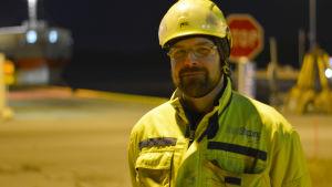 En man i gula arbetskläder och vit hjälm ute på hamnområde i Ingå. Tidig morgon och mörkt.