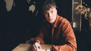 Nuori kiharatukkainen mies istuu pöydän ääressä ja katsoo suoraan kameraan. Päällään hänellä on terrakotan värinen kauluspaita ja rannekoruja käsissä.