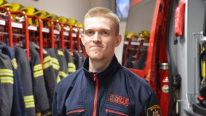 En brandman står bredbvid en barndbil inne i en brandstation.