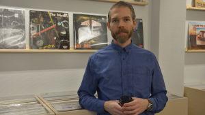 En man står framför en hylla med vinylskivor och ser in i kameran.