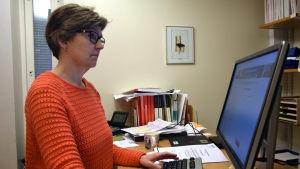 Carola Lindholm vid en dator.