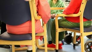 Seniorer på bäddavdelning sitter runt ett bord.