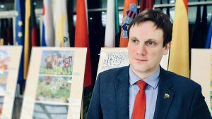 Den litauiske parlamentarikern Tomas Tomilinas står framför barnteckningar som är utställda i parlamentet Seimas.