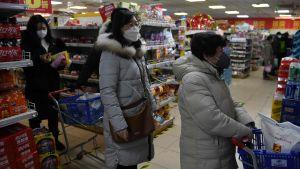Kunderna i kassakön i ett snabbköp i Peking bar alla skyddsmasker på söndagen.