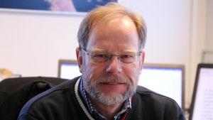 En medelålders man med glasögon och skägg.