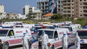 Frivilliga från Hizbollahs civilförsvar visade upp rörelsens ambulanser i mitten av april, i samband med coronakrisen. Bilden är tagen i Tyros, i södra Libanon och i bakgrunden ståtar ett porträtt av Irans andlige ledare Ali Khamenei.