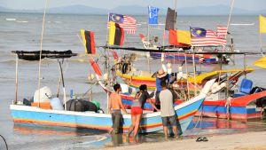 Färgglada fiskebåtar på en strand i Malaysia