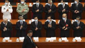 President Xi Jinping promenerar i förgrunden förbi ledamöter i den kinesiska Nationella folkkongressen. Ledamöterna har andningsskydd på sig.