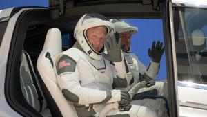 Astronauterna Douglas Hurley och Robert Behnken iklädda rymddräkter vinkar mot kameran.