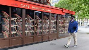 En man går utanför ett stängt kafé.