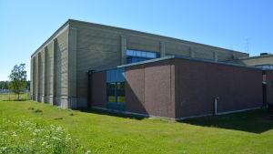 Baksidan av Kokonhallen, en gul och brunaktig fyrkantig byggnad.